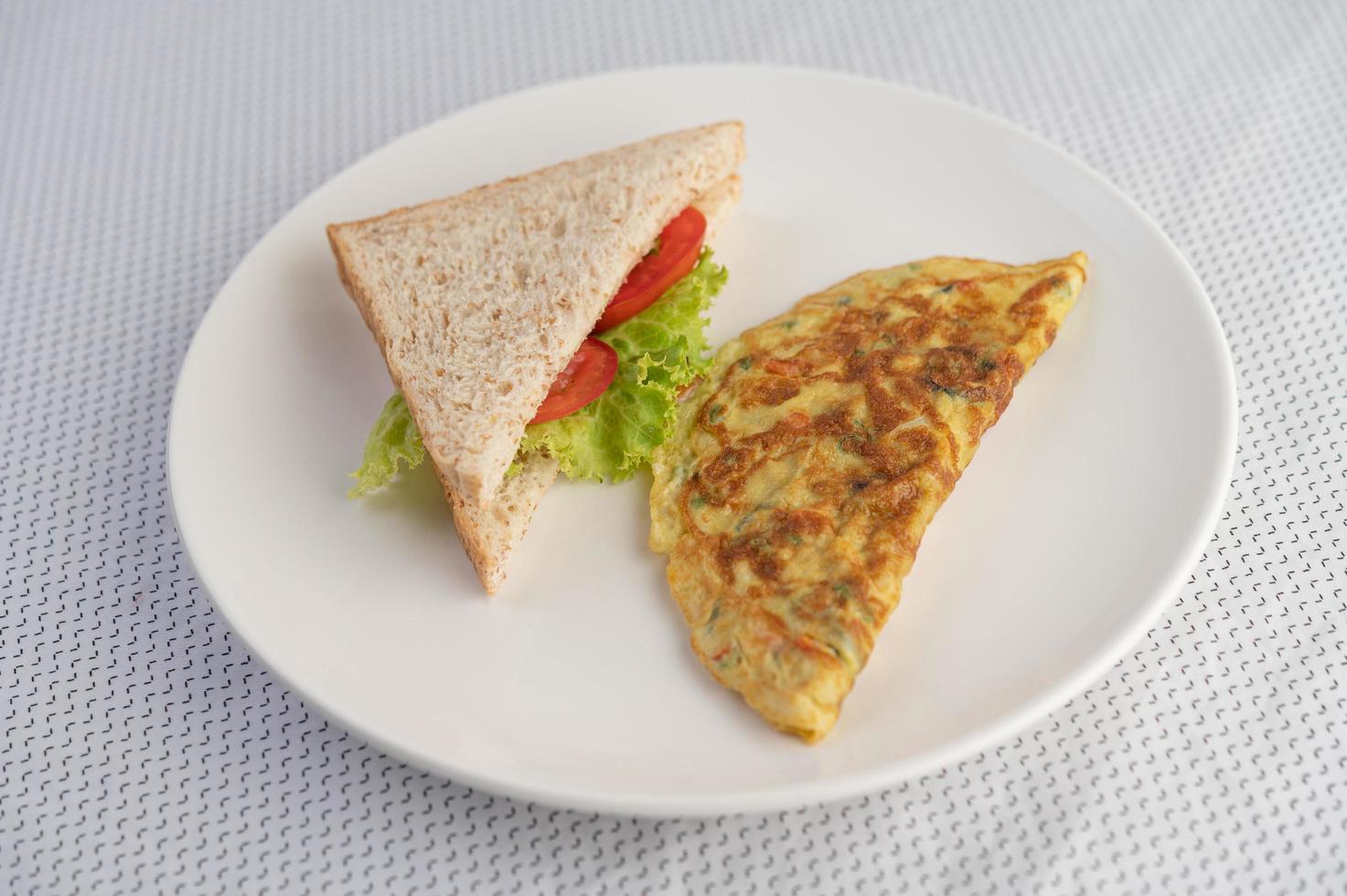 een ei-omelet en sandwich op een witte plaat foto