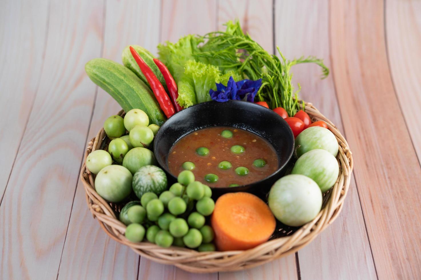 chilipasta in een kom met aubergine, wortelen, chili en komkommers in een mandje foto