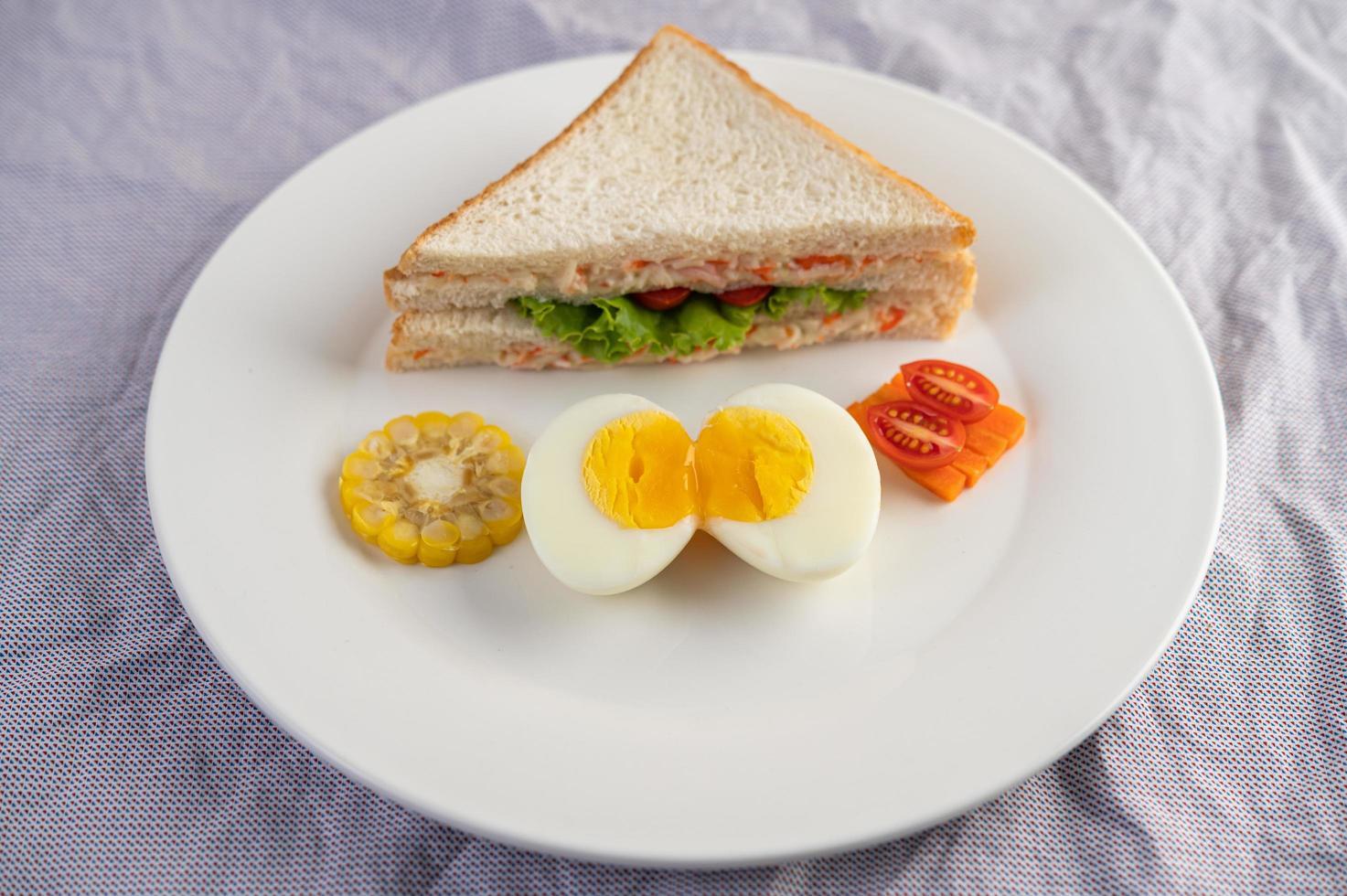 gekookte eieren, maïs, tomatensandwich op een witte plaat foto