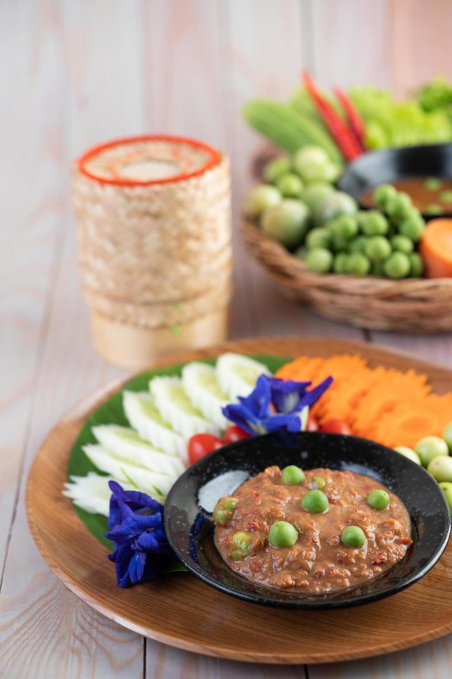 chilipasta in een kom met aubergine, wortelen, chili en komkommers foto