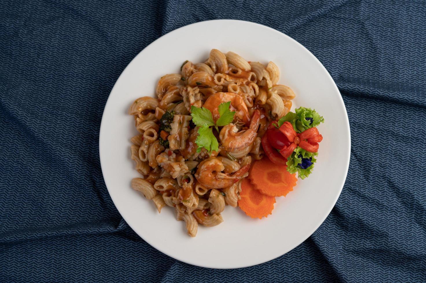 garnalen en macaroni met wortelen, tomaten en salade foto