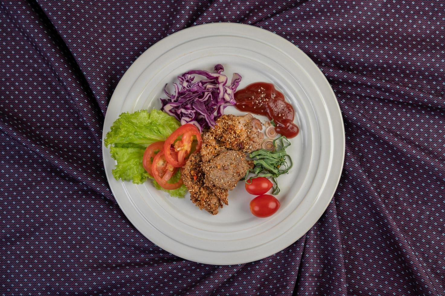 Varkenssalade met paprika, tomaat, citroen, limoen, knoflook en salade foto