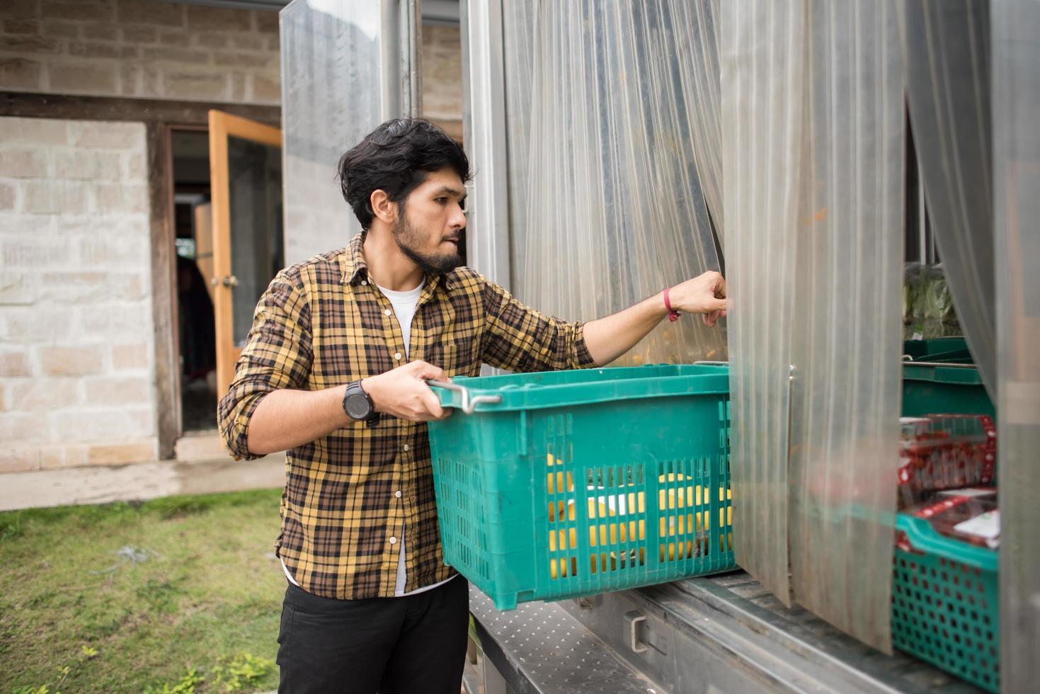 portret van een hipster boer met een doos met fruit te koop op de markt foto