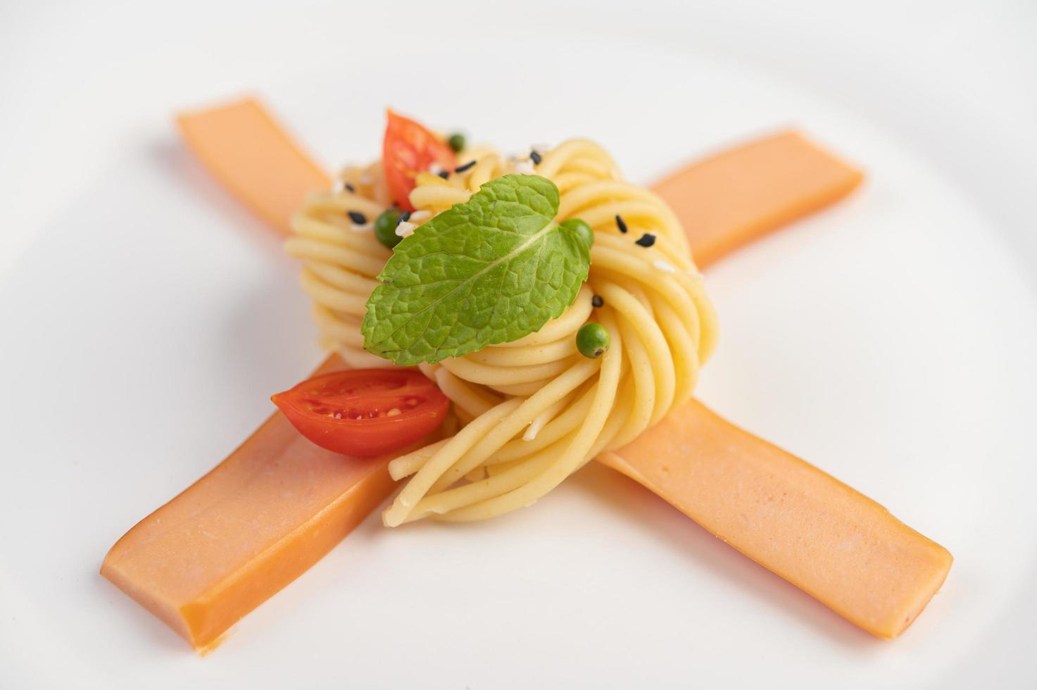 gastronomische spaghetti prachtig gerangschikt op een witte plaat foto