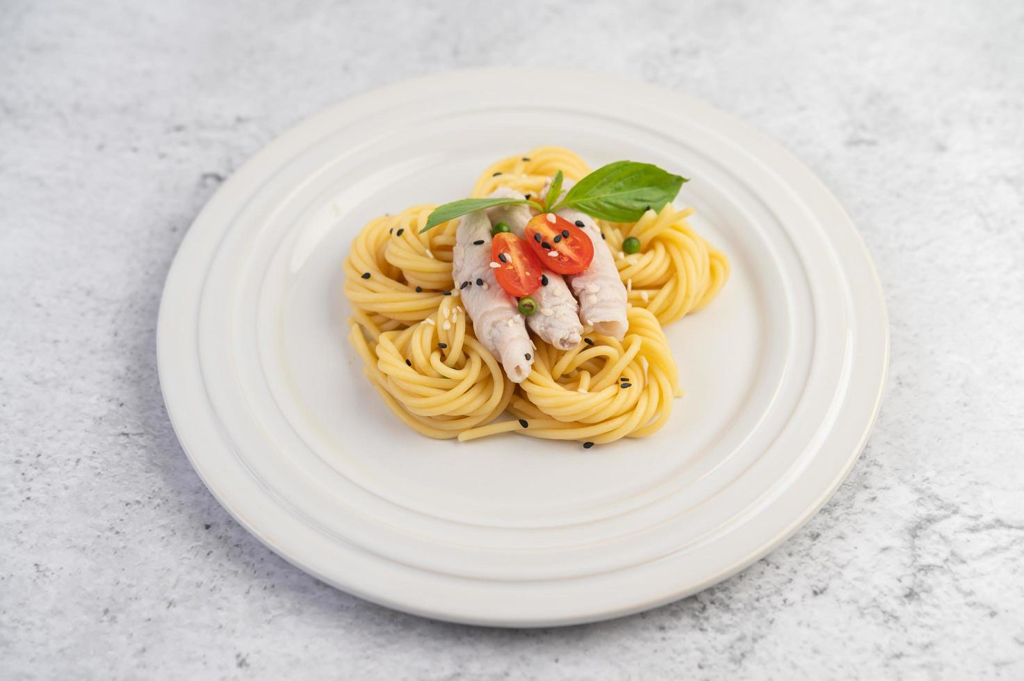 vergulde spaghetti en varkensvlees gerangschikt op een witte plaat foto
