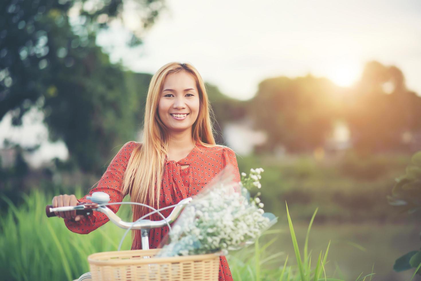 jonge Aziatische vrouw fietsen in een park foto