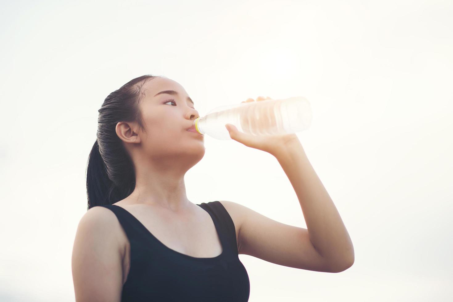 jonge fitness tiener drinkwater na het uitvoeren van oefening foto