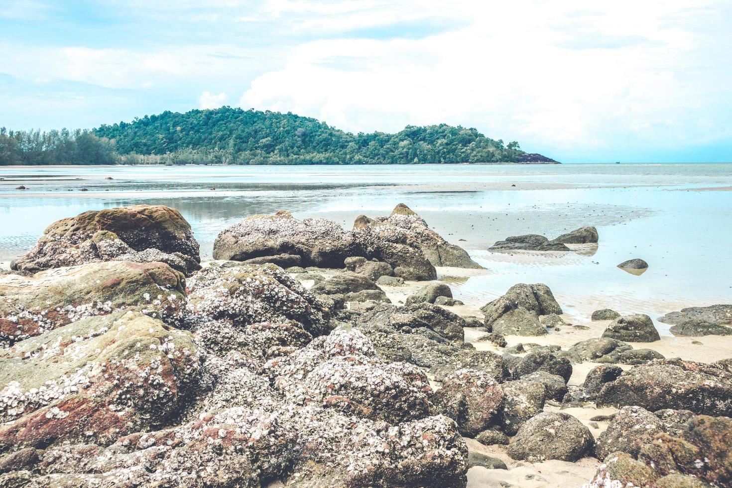 rotsen op strand met bewolkte blauwe hemel foto