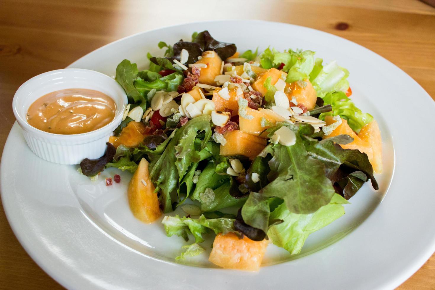 salade en dressing op witte schotel foto
