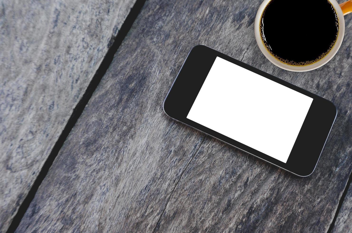 bovenaanzicht mobiele telefoon en koffiekopje foto