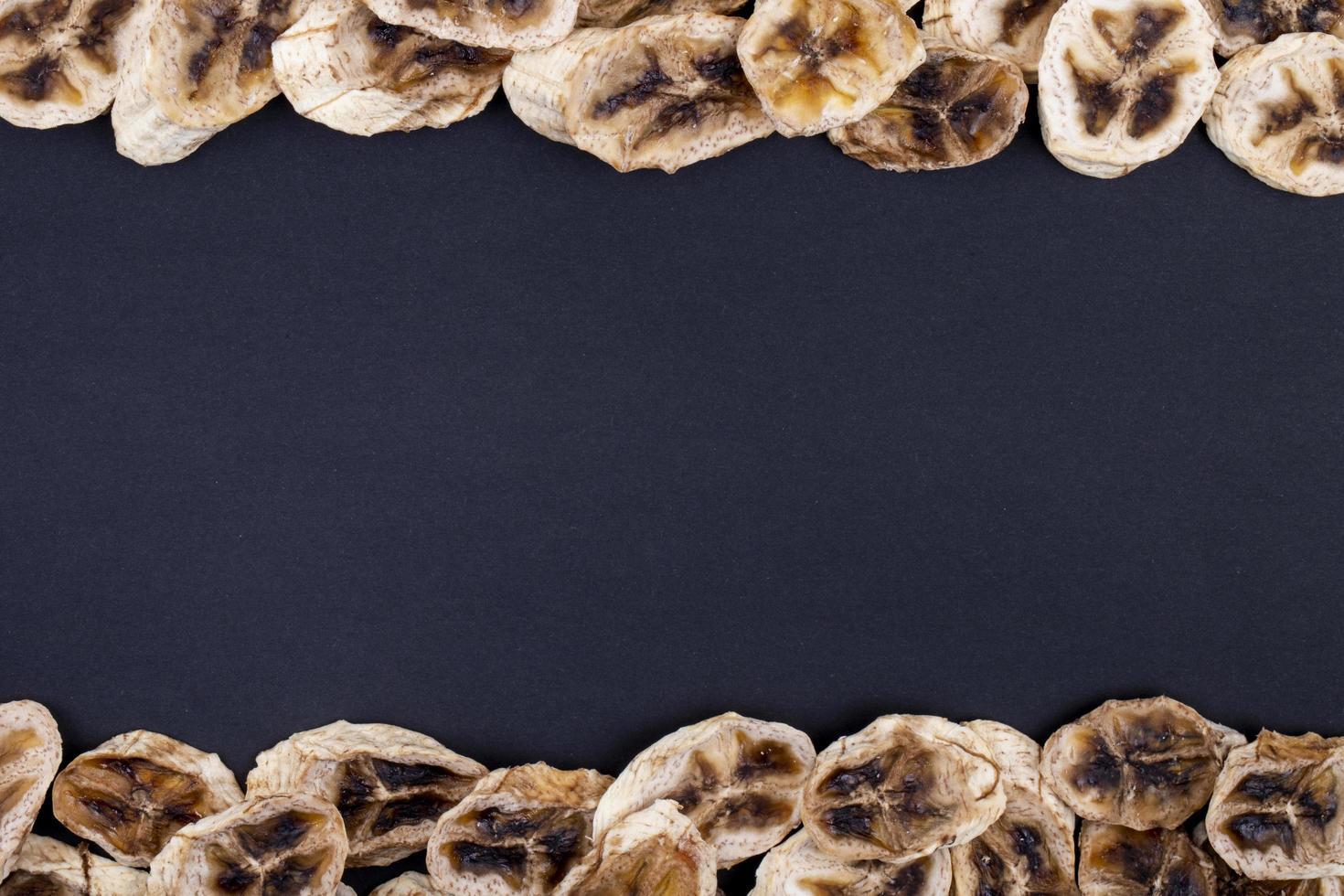 bovenaanzicht van gedroogde bananenchips geïsoleerd op zwarte achtergrond met kopie ruimte foto