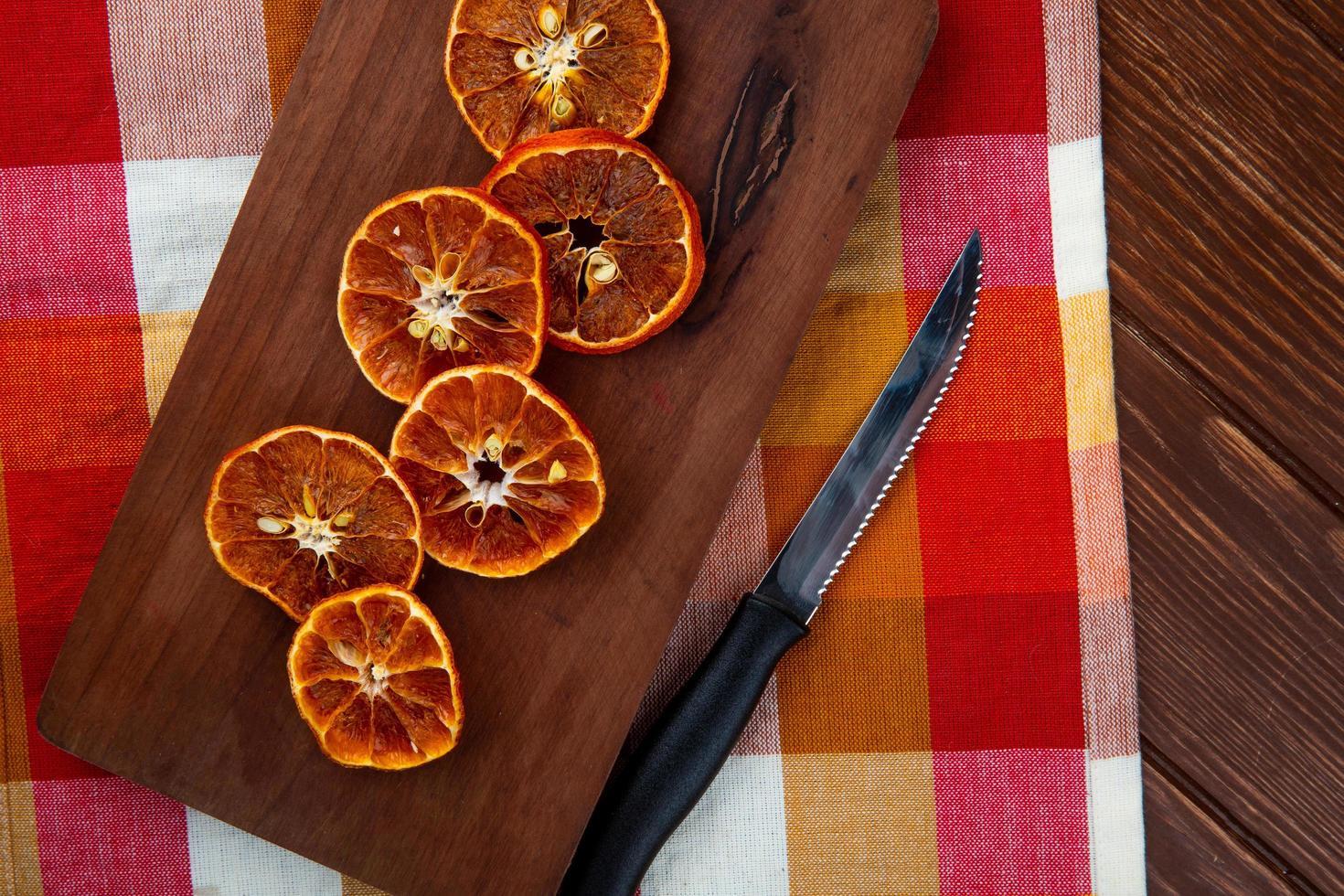 bovenaanzicht van gedroogde stukjes sinaasappel met keukenmes op een houten snijplank op geruite tafellaken foto