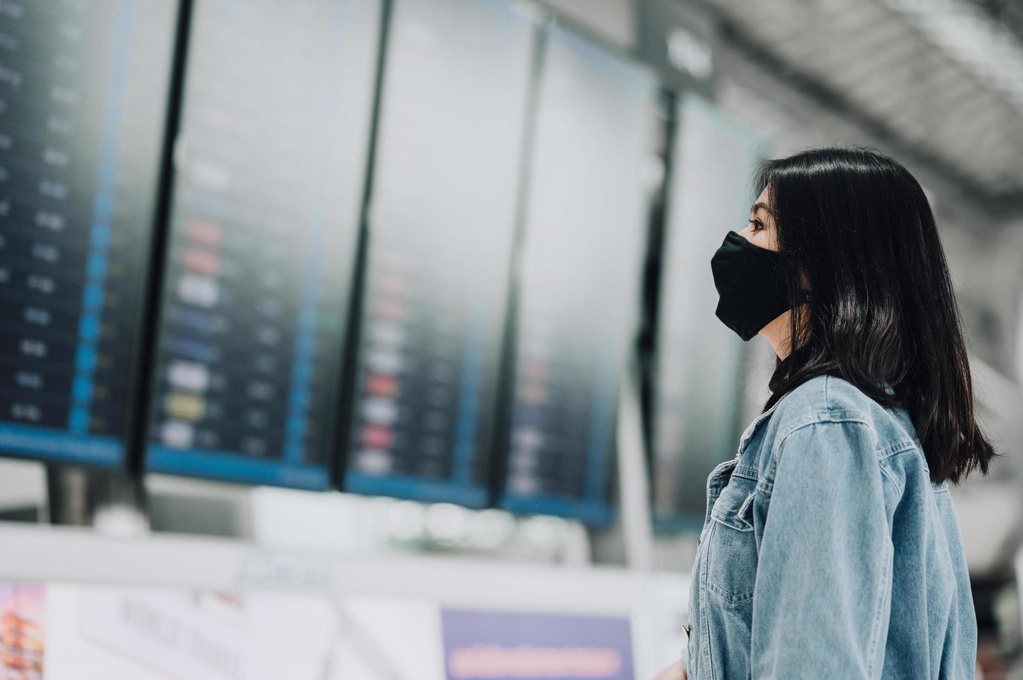 vrouw die masker draagt dat vluchtinformatie bekijkt foto