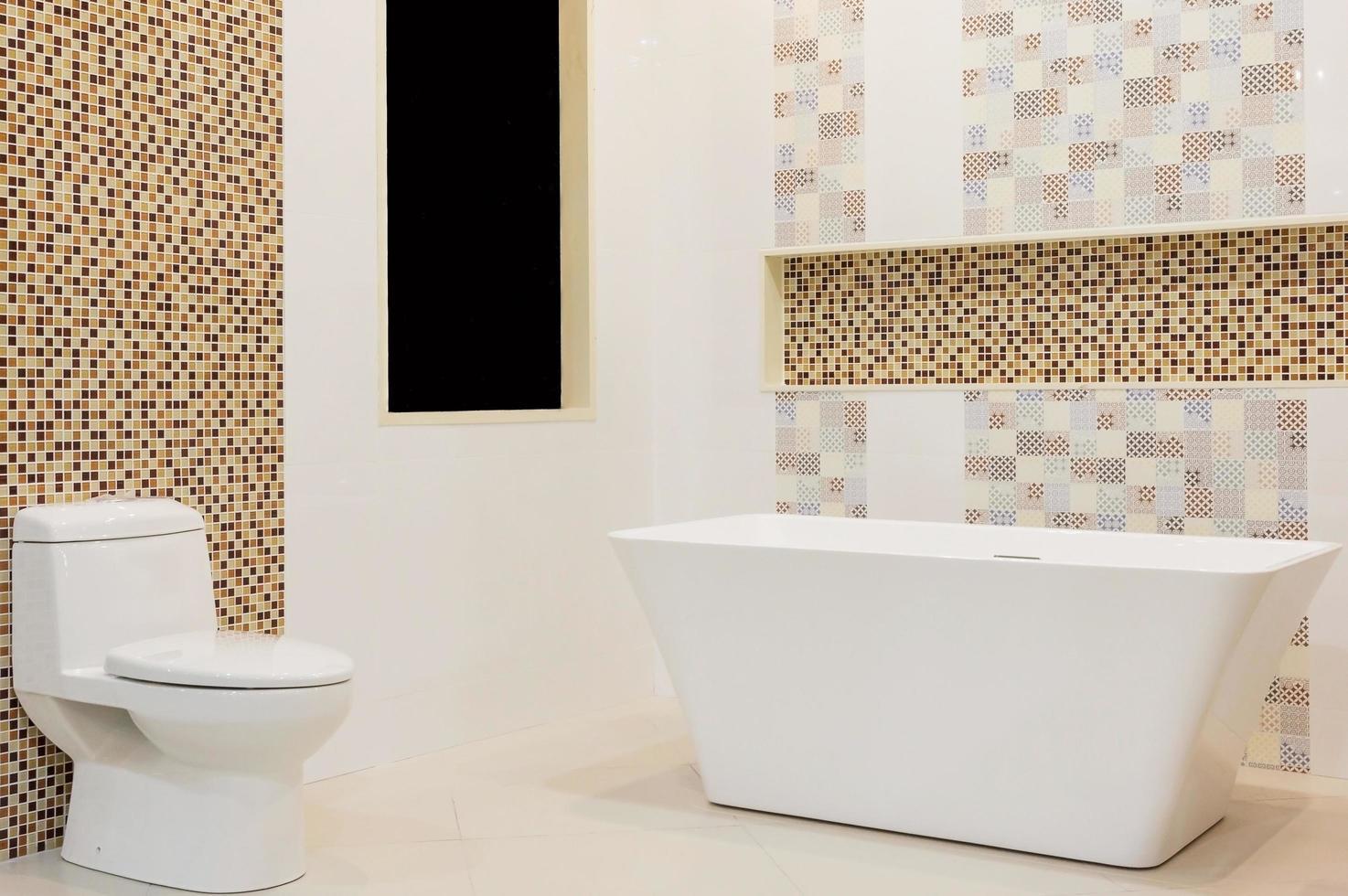 luxe wit badkamerinterieur met witte tegels, spiegel, een wastafel en een wit bad. concept van ontspanning. foto