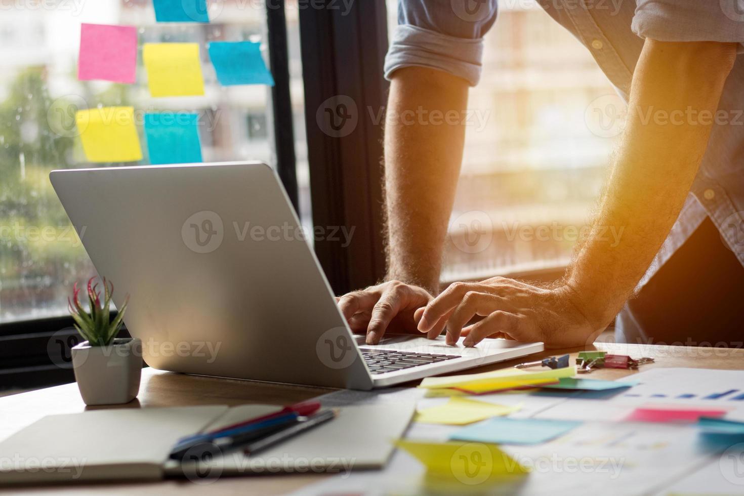man met behulp van een laptop in een thuiskantoor foto