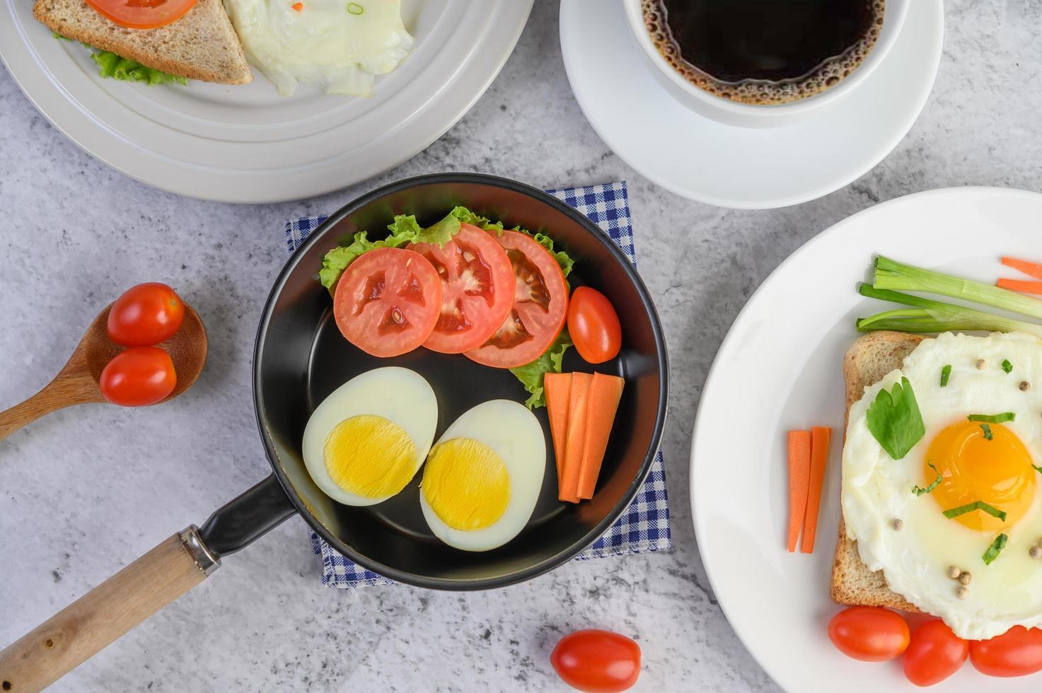 gekookte eieren, wortelen en tomaten met lepel en koffiekopje foto