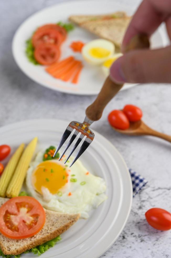 vork reiken naar gebakken eieren met brood met groenten als ontbijt foto