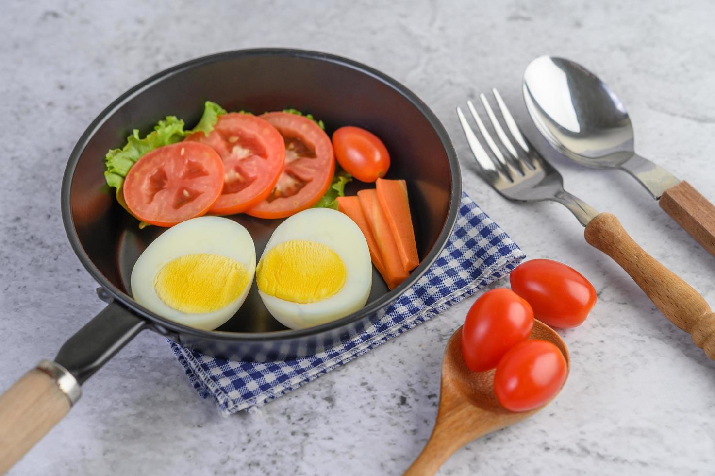 gekookte eieren, wortelen en tomaten in een pan met tomaten foto