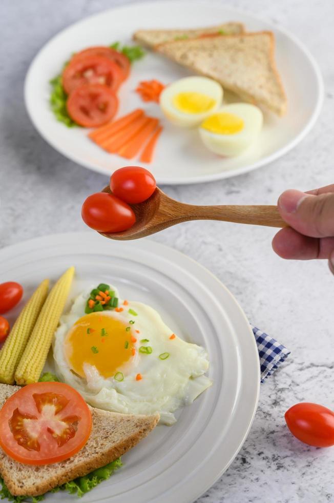 gebakken eieren, brood, wortelen en tomaten op een witte plaat foto