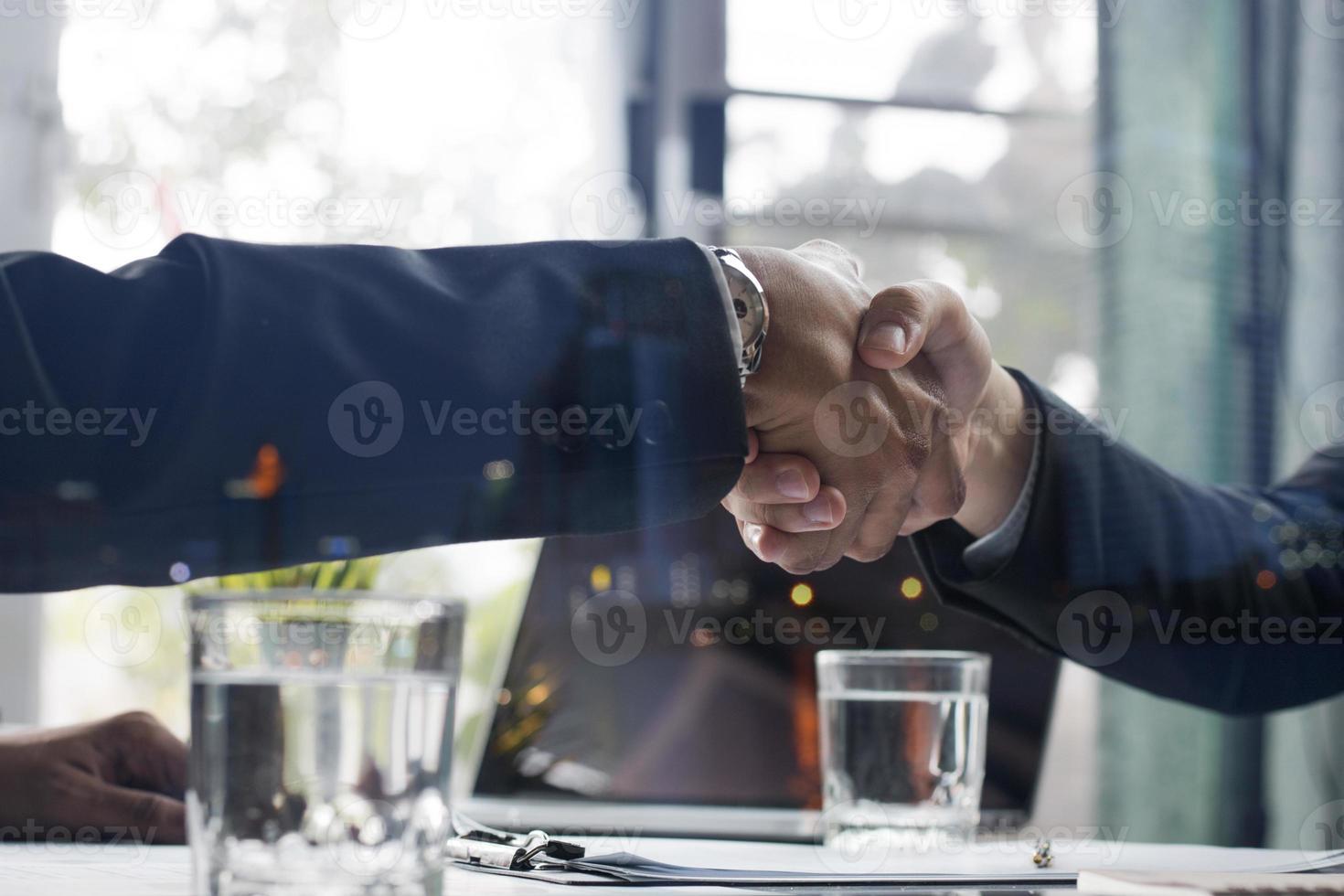 twee zakenmensen handen schudden over een deal foto