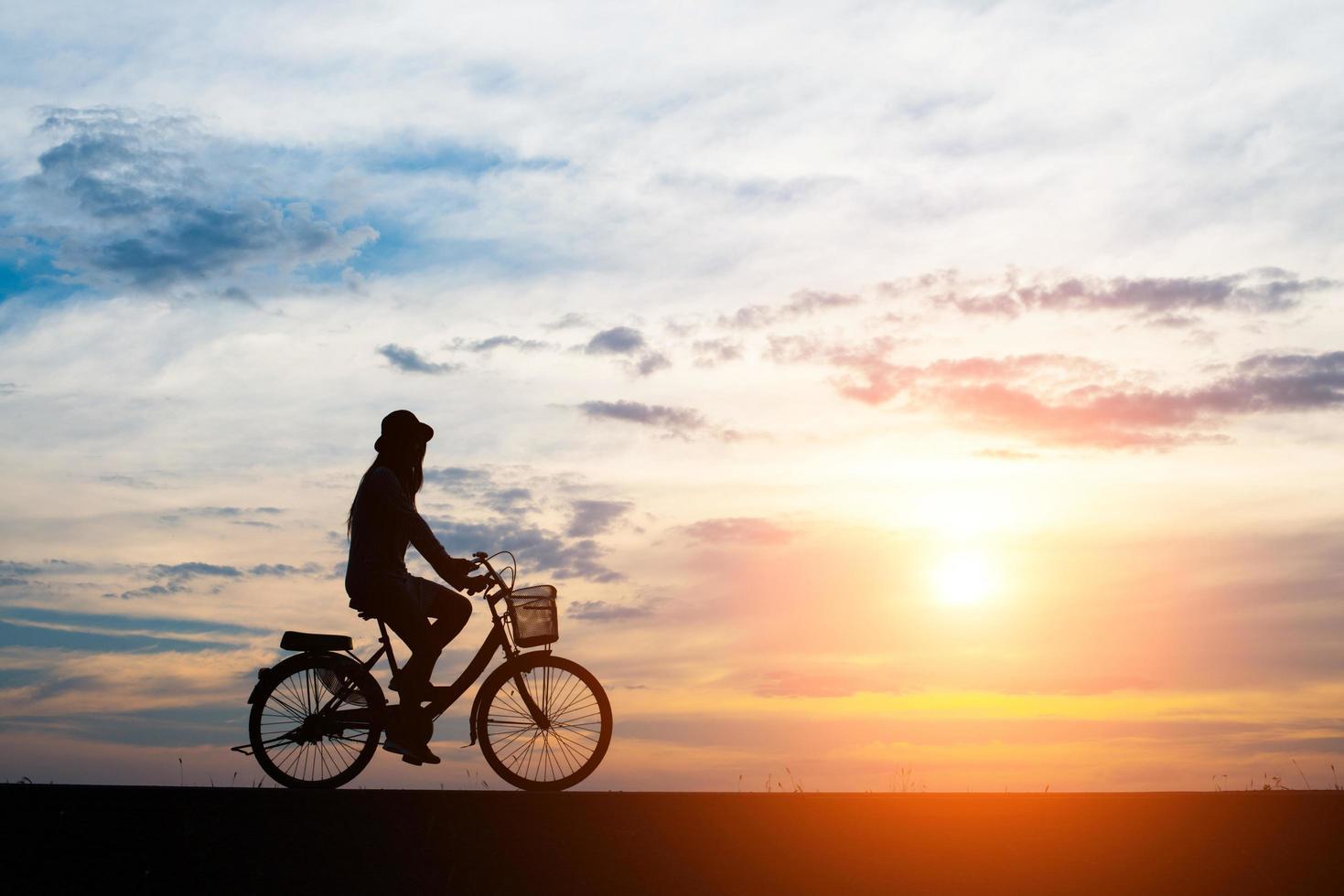 jonge man rijdt op een fiets op zonsondergang achtergrond foto