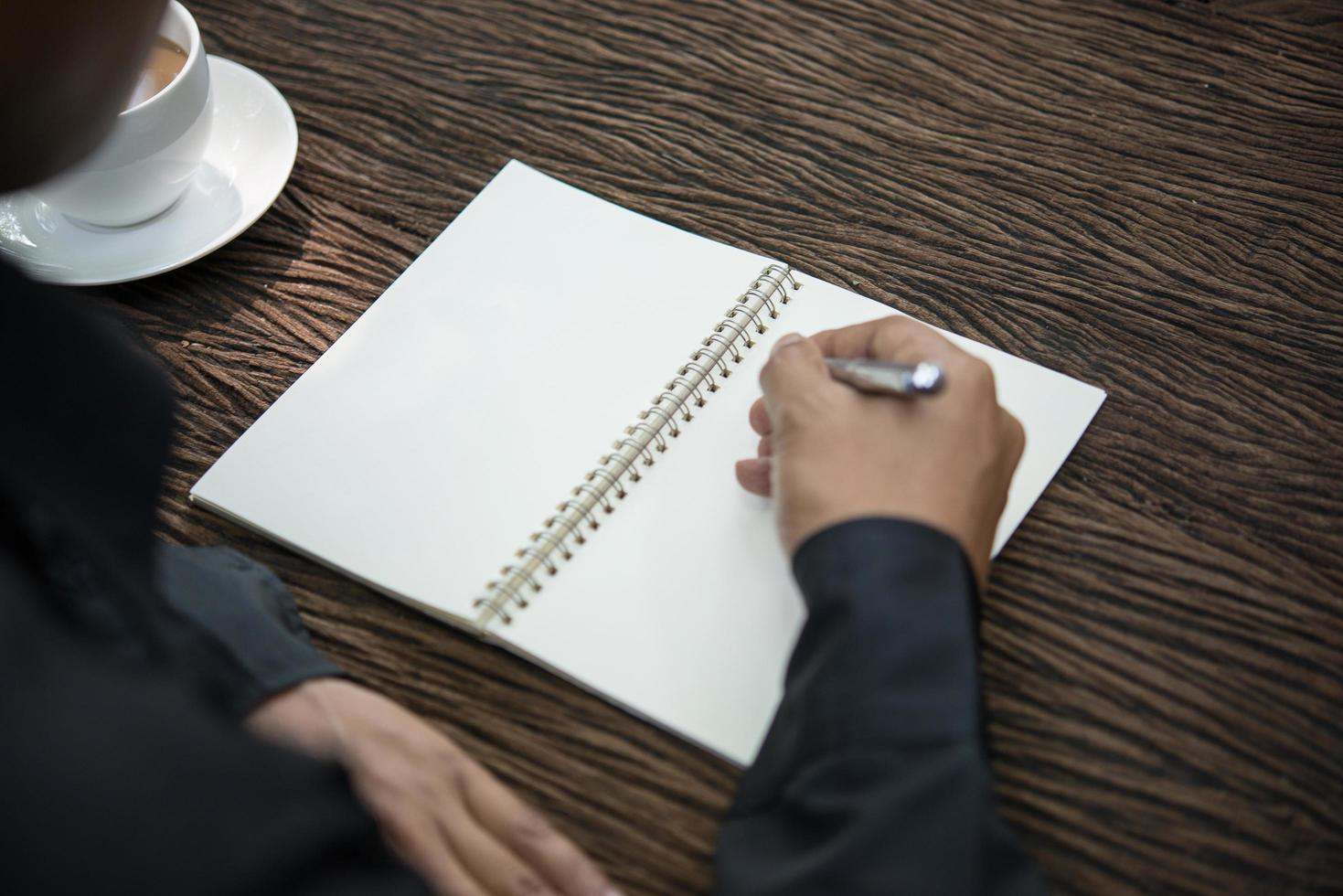 jonge man schrijven op een notebook die werkt aan een rustieke houten tafel foto