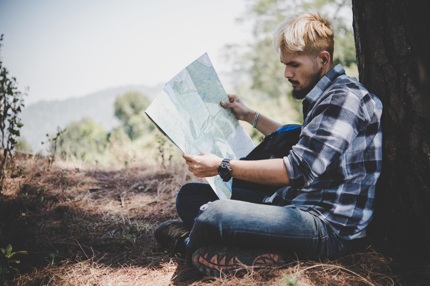 wandelaar ontspannen door boom kijken naar kaart foto