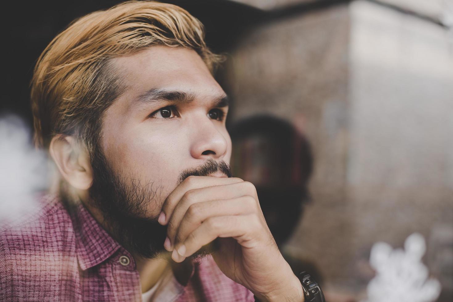 jonge hipster man zit in coffeeshop denken en wegkijken foto