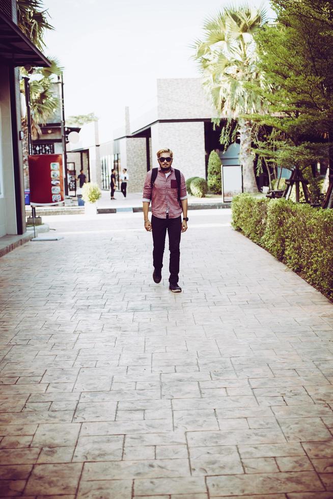 portret van een knappe hipster man in spijkerbroek en zonnebril lopen foto