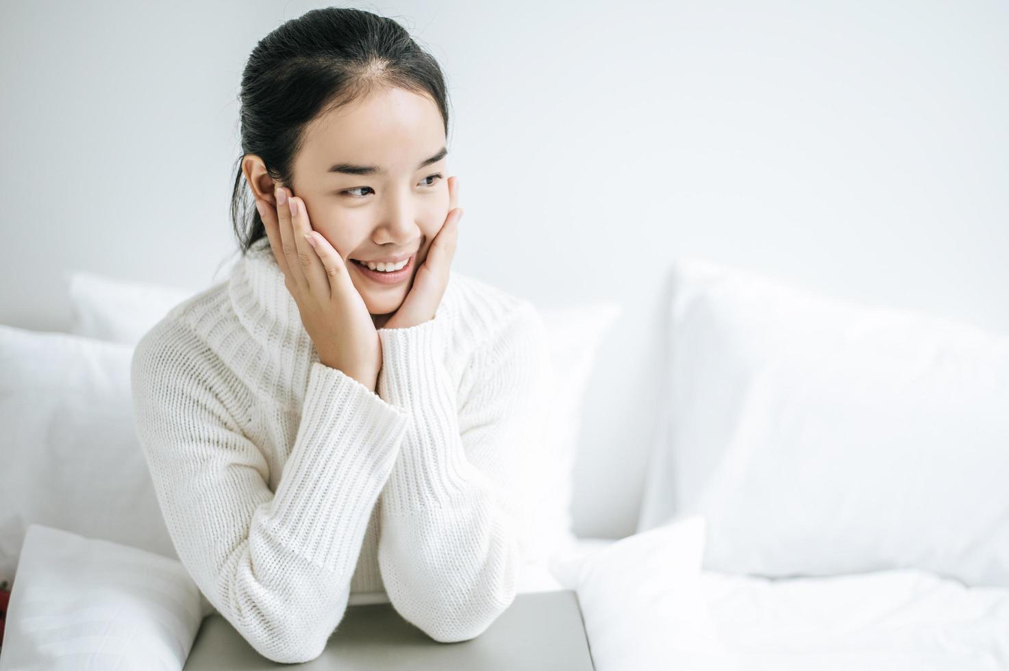 jonge vrouw zittend op haar bed met handen aanraken van wangen foto