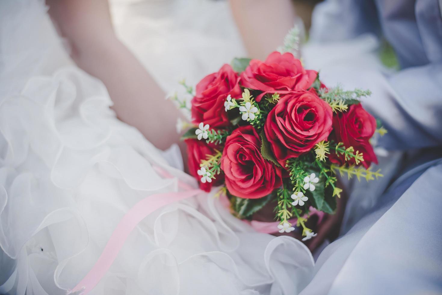 bruid heeft een bruiloft rode roos boeket in handen foto