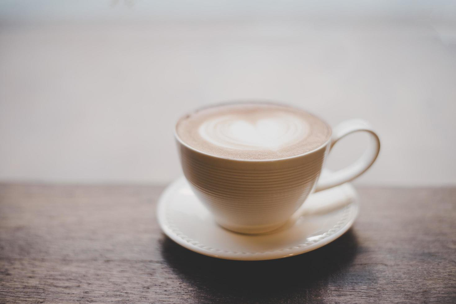 vintage latte art koffie met hartvorm op houten tafel foto