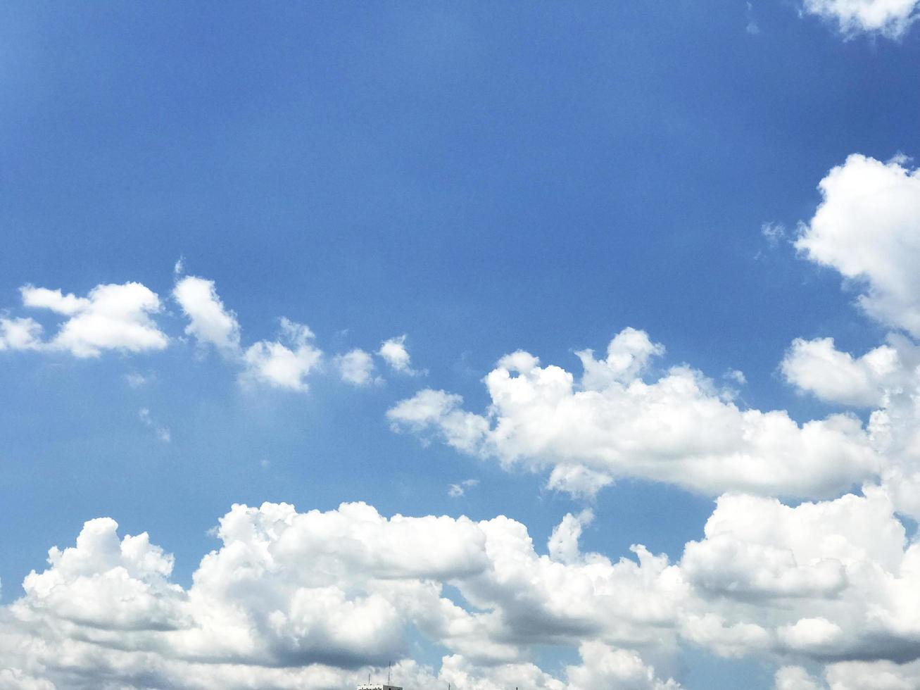 blauwe lucht met pluizige witte wolken foto