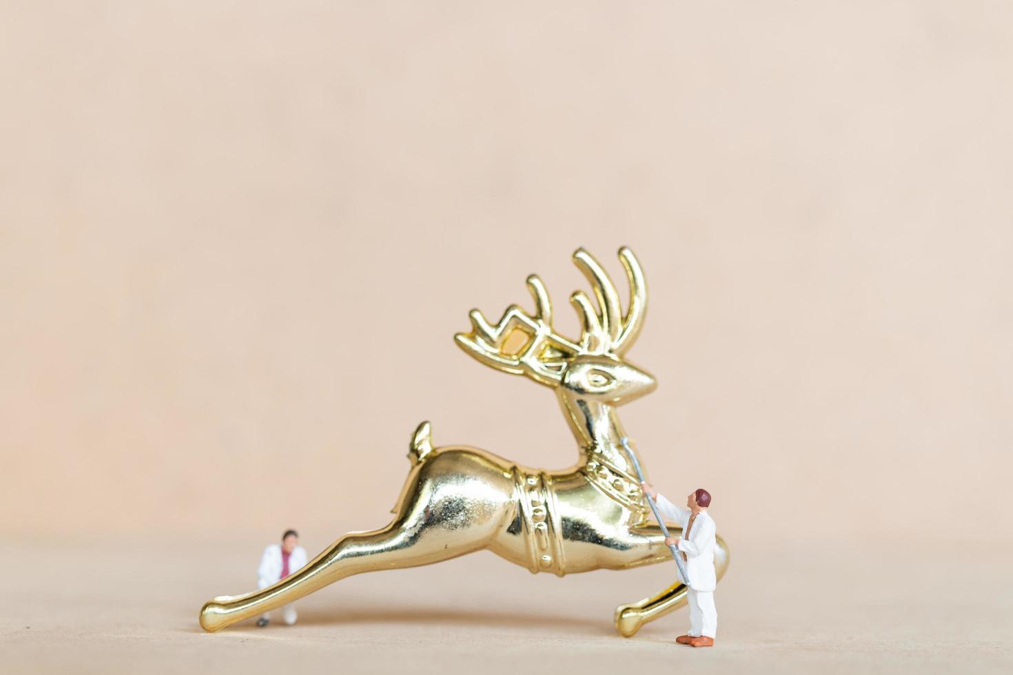 miniatuurmensen die aan kerstversieringen werken foto