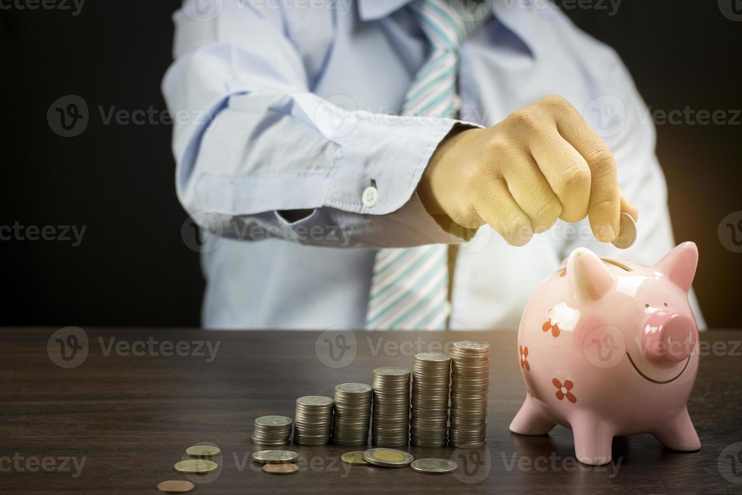 persoon die munten in een spaarvarken zet foto