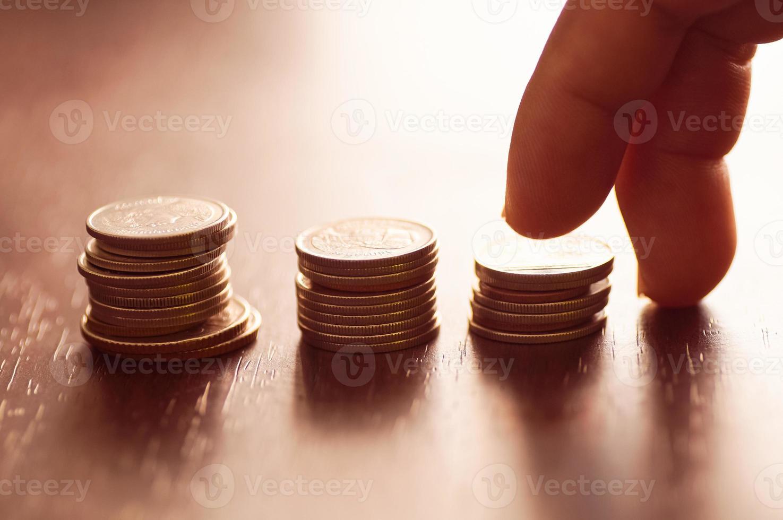 vingers die stapels munten opvoeren foto