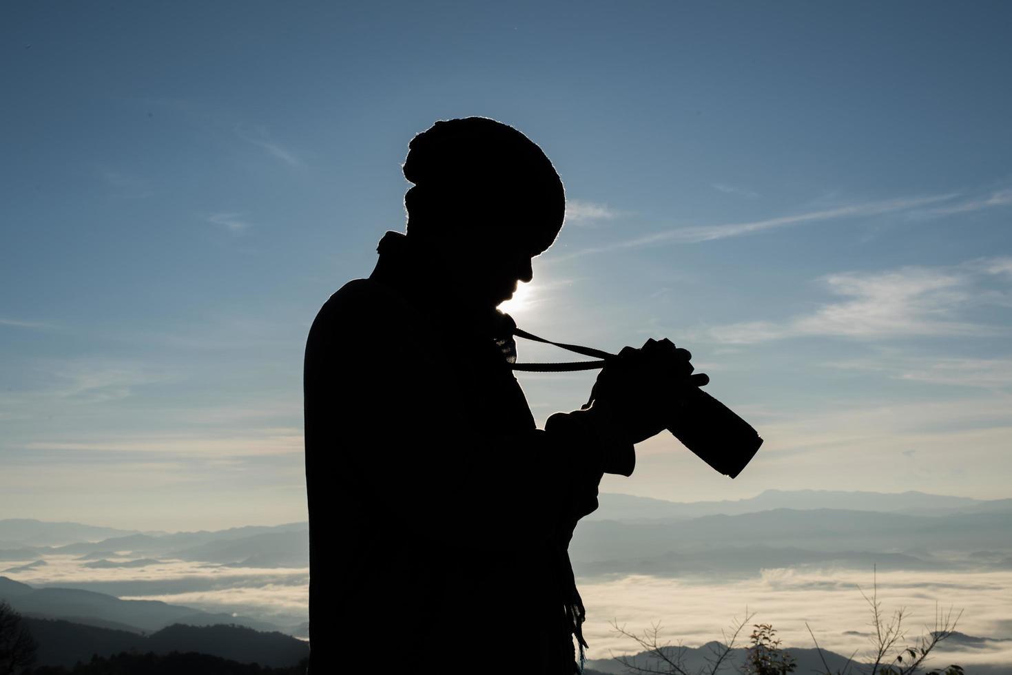 silhouet van jonge fotograaf met een camera met berglandschap foto