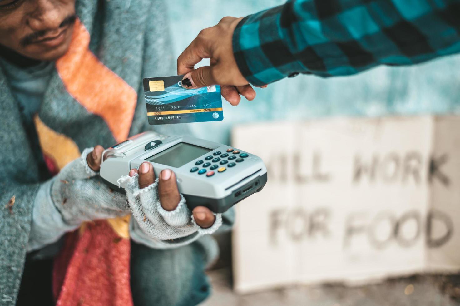 bedelaars die onder het viaduct zitten met een creditcard en een creditcard-veegmachine foto