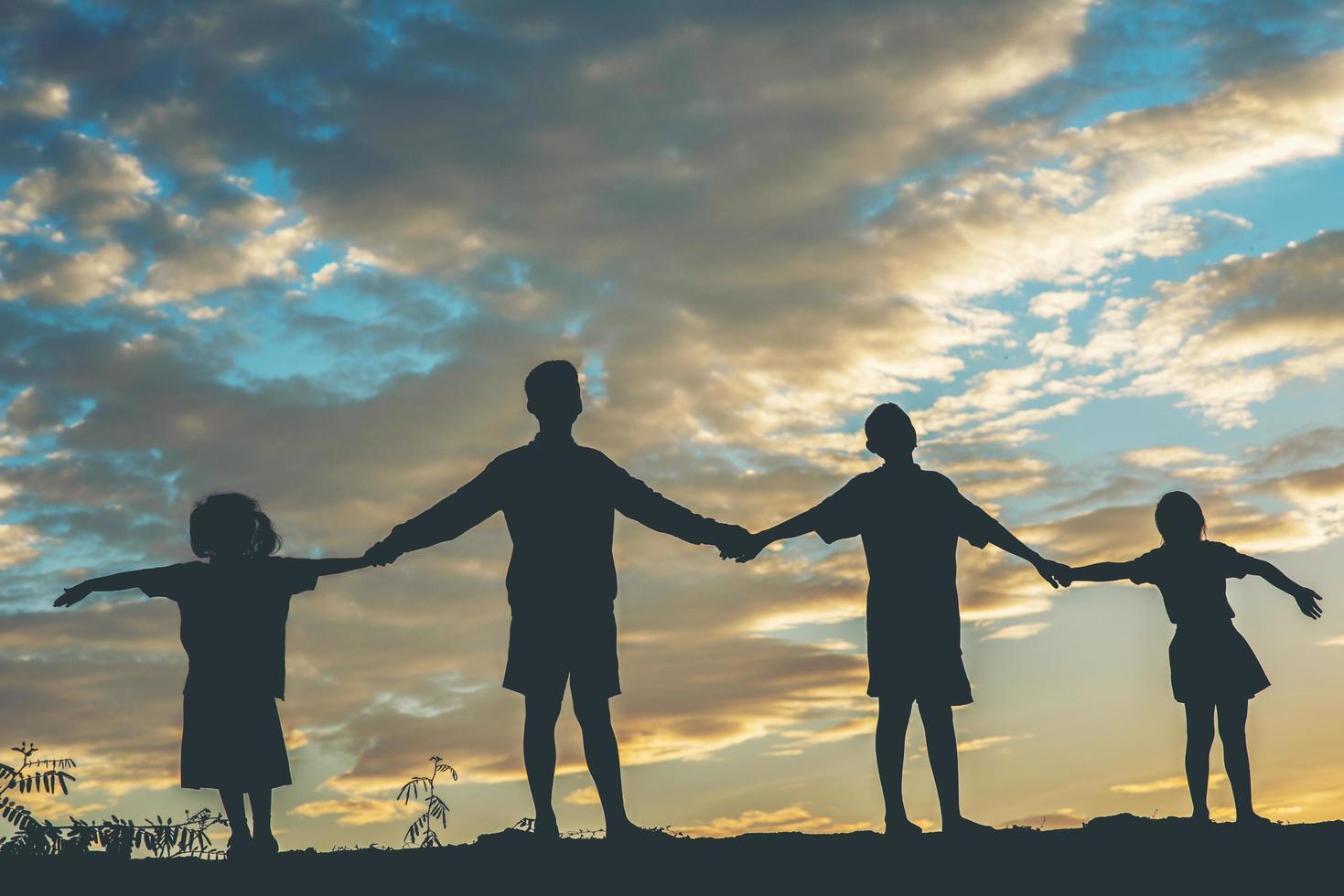 zonsondergang silhouet van spelende kinderen foto
