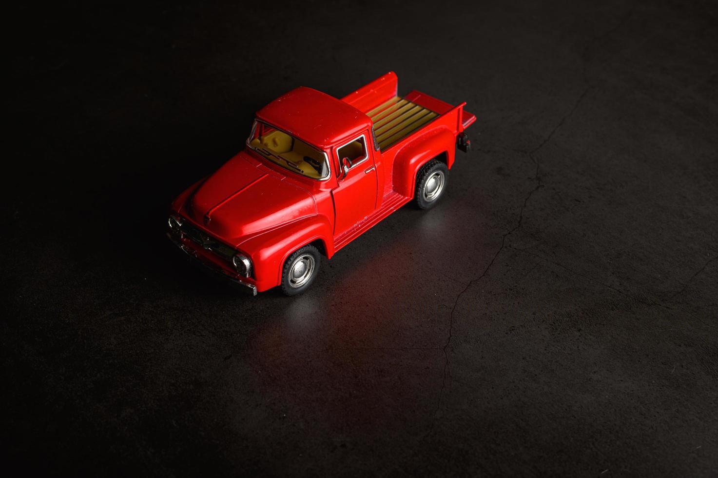 rode pick-up model vrachtwagen op een zwarte vloer foto