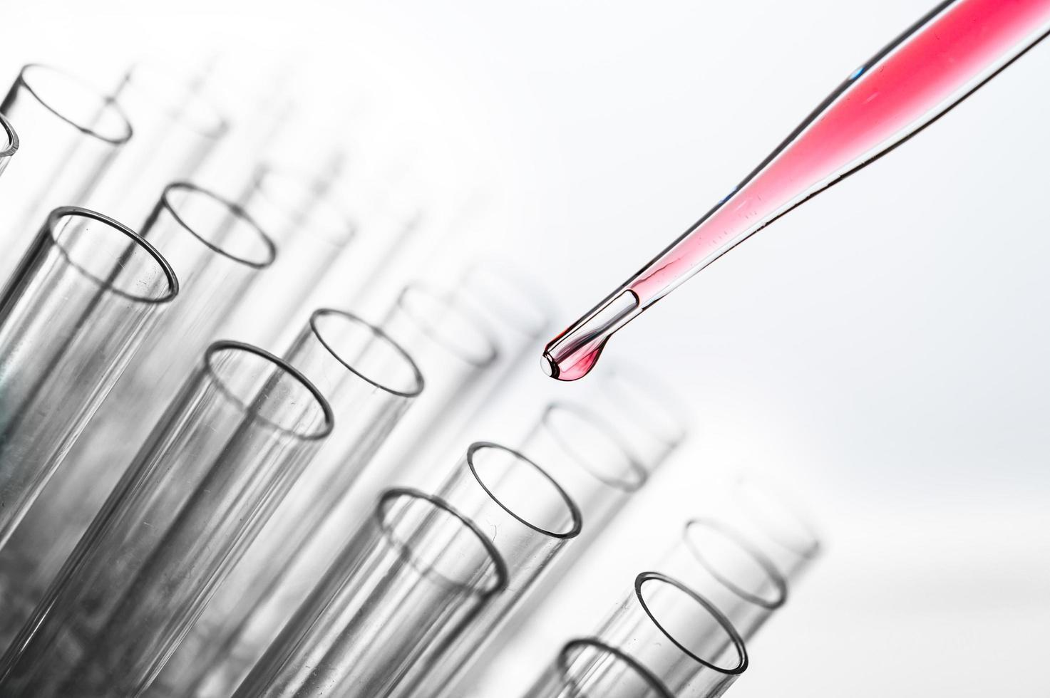 roze chemicaliën vallen in een beker foto