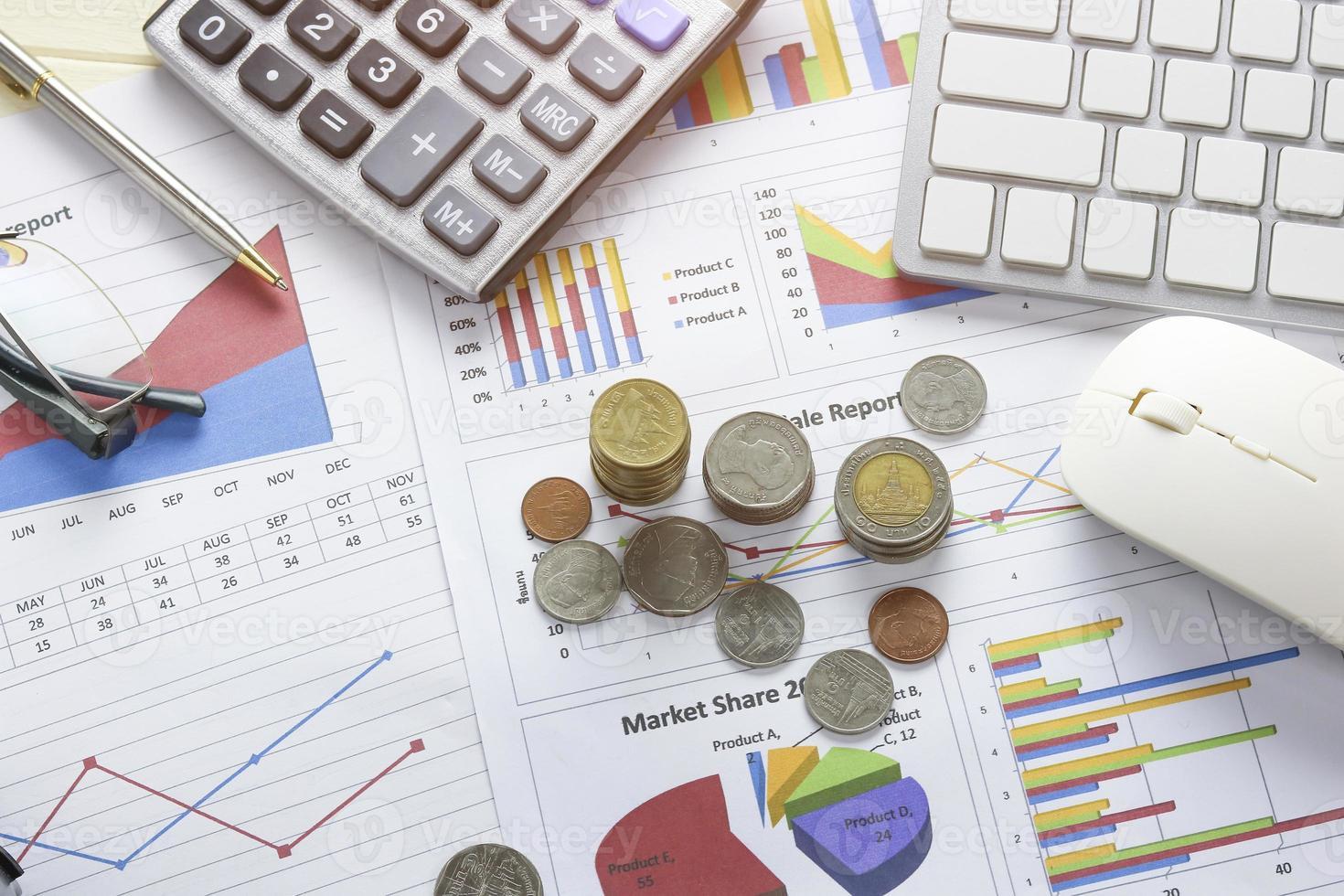 munten op het bureau met grafieken en toetsenbord foto