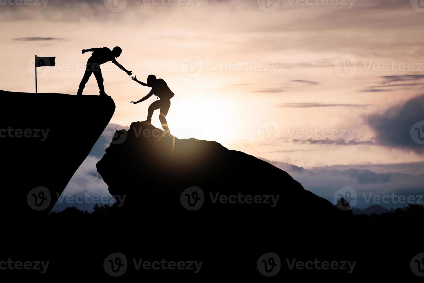 twee mensen helpen elkaar een berg te beklimmen foto