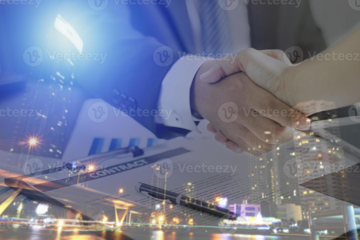 twee zakenlieden handen schudden met nachtelijke stad overlay foto