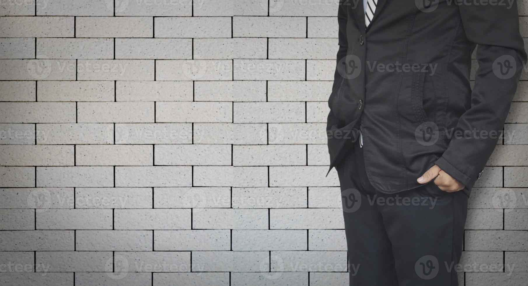 zakenman staande op bakstenen muur achtergrond met kopie ruimte foto