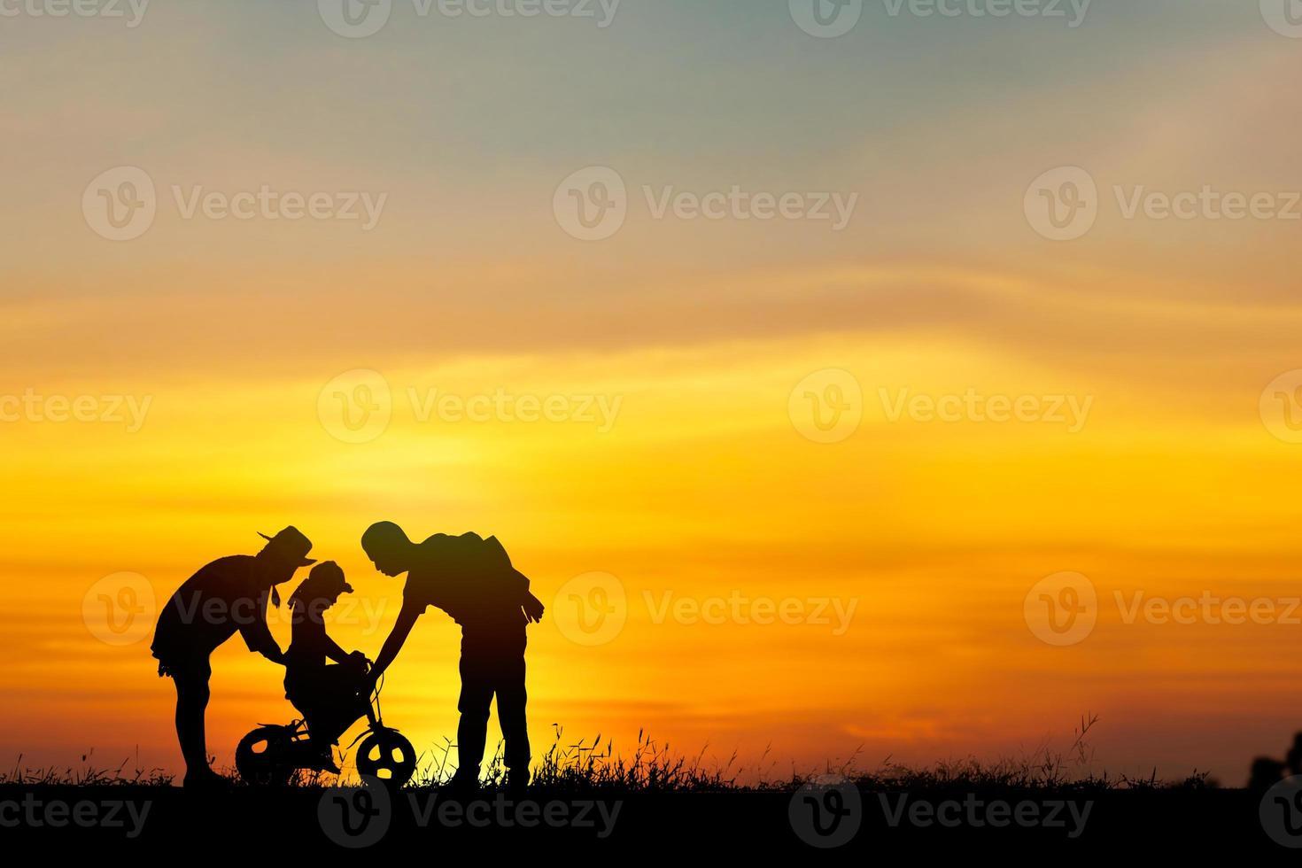 silhouet van ouders helpen dochter fietsen foto