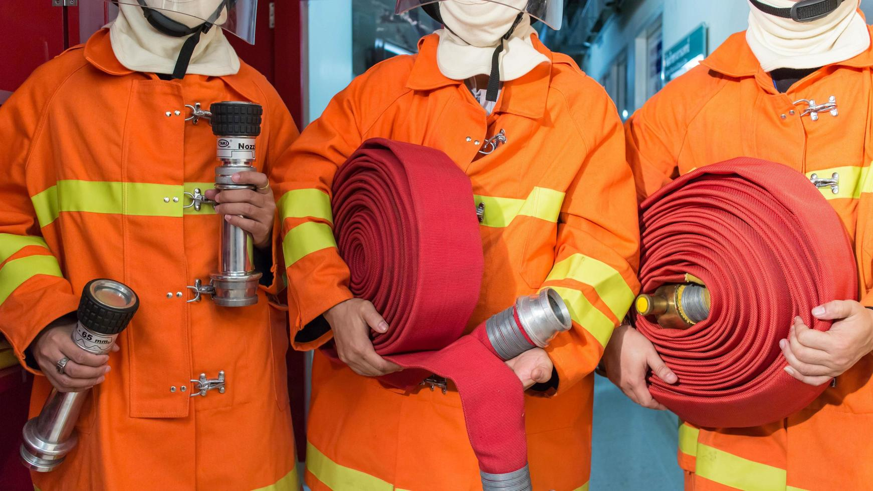 brandweerlieden in uniforme holdingsuitrusting foto