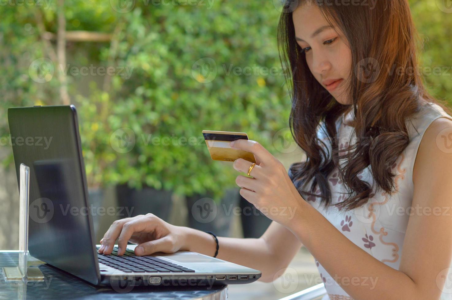 Aziatisch meisje creditcard bedrijf en met behulp van laptop foto