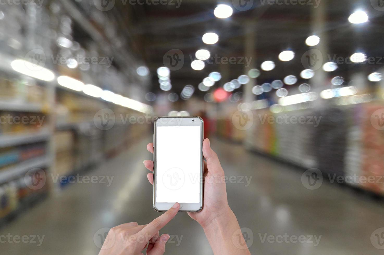 handen met behulp van de mobiele slimme telefoon leeg scherm met onscherpe achtergrond in de supermarkt foto