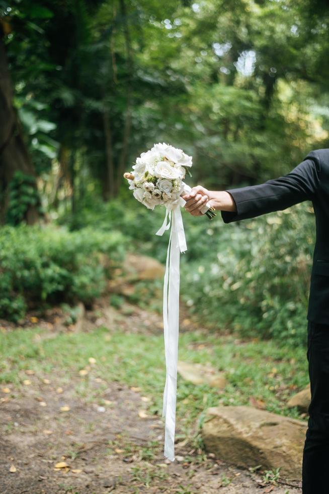 close-up van bruidegom met mooi boeket in handen voor bruid foto